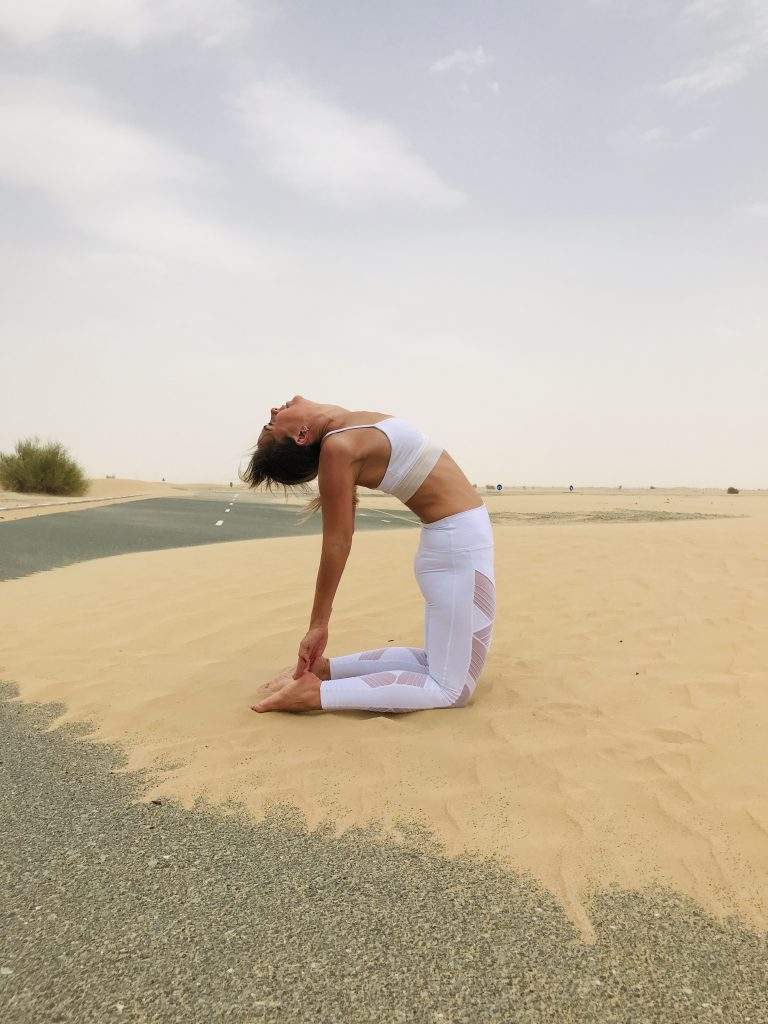 Camel yoga posture in the desert